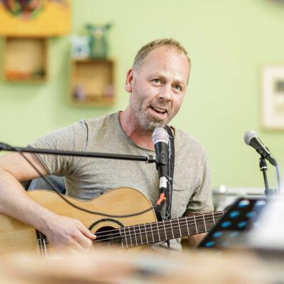 Foto: Sitzender Sänger mit Gitarre, David Schnittker, Diakonie Münster