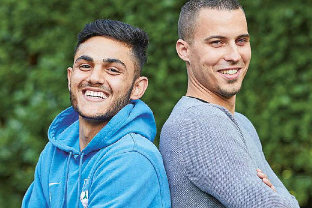 Foto: Zwei lachende junge Männer stehen Rücken an Rücken