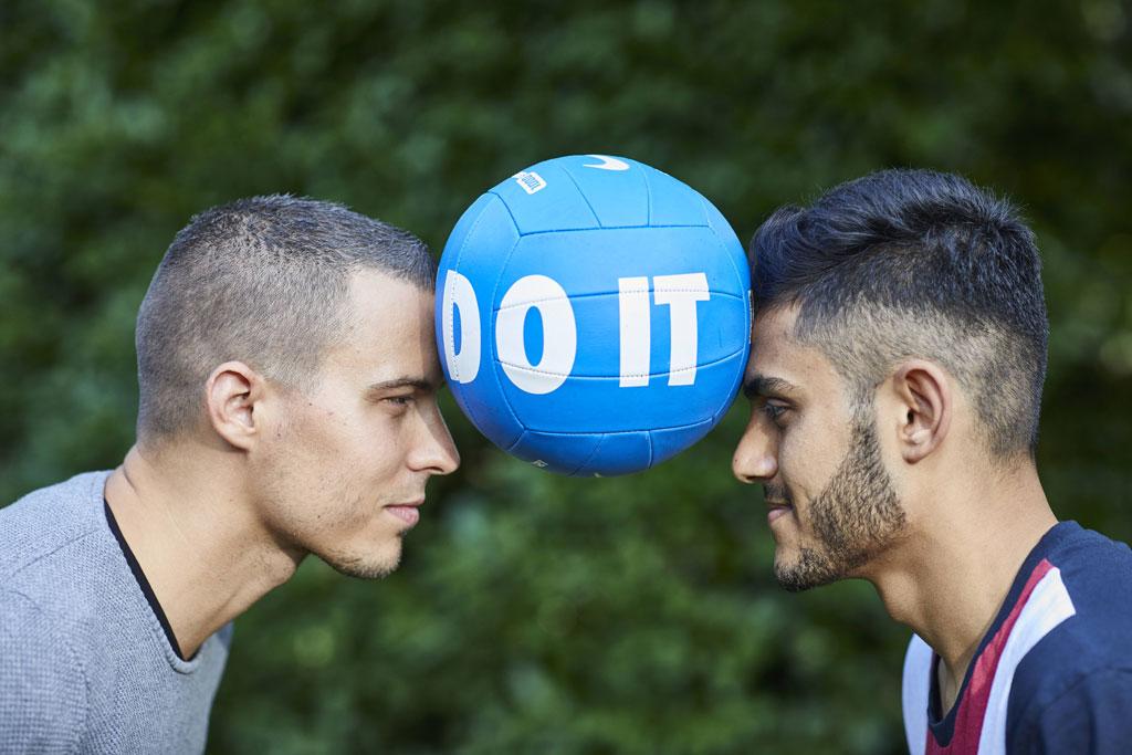 Foto: Zwei Junge Männerköpfe mit einem Ball in der Mitte, Teamkoordinater Balazs Petik mit Bilal