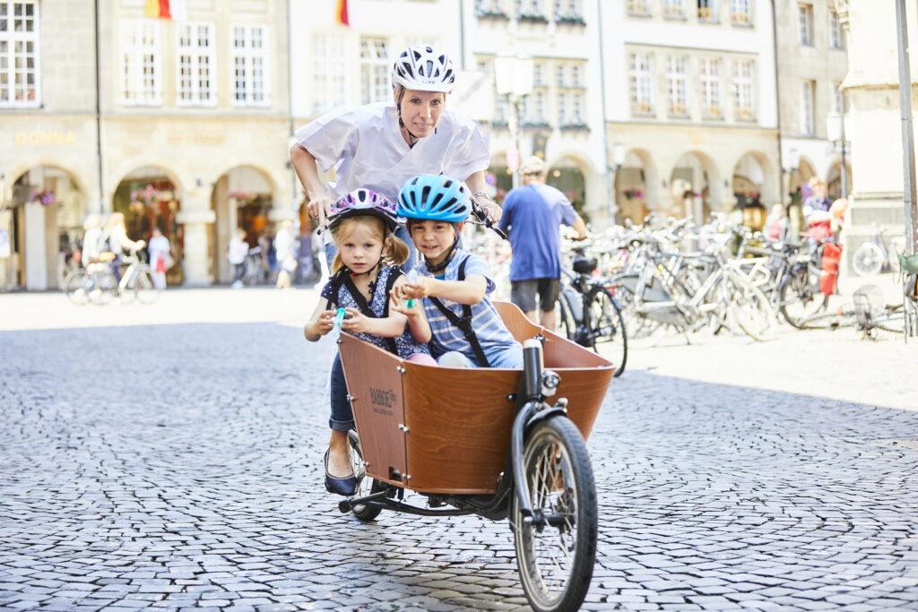 Foto: Mutter, Mitarbeiterin der Diakonie Münster, mit Lastenfahrrad transportiert ihre zwei Kinder